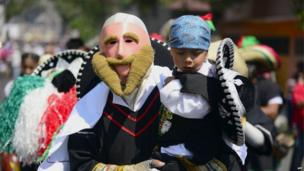 A man wearing a mask and costume is carrying a child at the Cinco de Mayo celebrations in Mexico City
