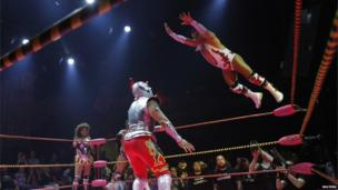 A lucha libre wrestler leaps through the air at the Mayan Theatre in Los Angeles