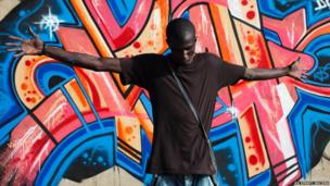 Graffiti artist Diablos poses for a picture in front of a mural next to a highway in Dakar