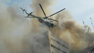 A Pakistani army helicopter rescues a man from a burning building in Lahore