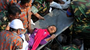 A woman being taken away on a stretcher having been rescued from a collapsed building in Dhaka