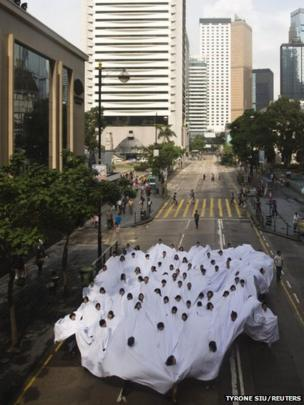 People wearing a white cloth take part in an art installation in Hong Kong