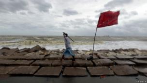 A Bangladeshi volunteer holding a stick walks along the Bay of Bengal coast to evacuate people in Chittagong, Bangladesh