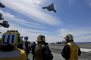 A Navy X-47B drone above the USS George HW Bush