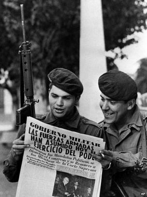 Two army soldiers read a newspaper in the Buenos Aires Plaza de Mayo March 24, 1976 after a military coup led by Gen Jorge Rafael Videla ousted President Isabel Peron.