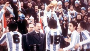 Jorge Rafael Videla (L) presents the World Cup trophy to Argentine national soccer team captain Daniel Passarella after the Argentine vs Netherlands match on June 25, 1978