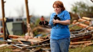 Rachel Hilton holds stray kittens found in the debris
