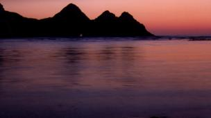 Three Cliffs Bay silhouetted against the sunset