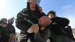 Riot police detain a supporter of Ukraine's opposition following a rally in Kiev