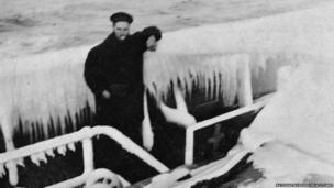 Sailor posing for the camera on-board a ship heavily laden with ice.