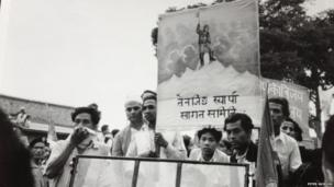 A Nepalese banner, carried by a crowd, depicting Tenzing alone at the top of Mount Everest