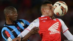 Wilder Medina of Colombia's Santa Fe vies for the ball with Peru's Real Garcilaso player Joel Herrera