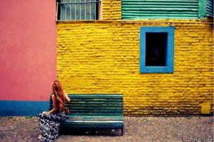 A woman seated in front of a coloured wall in Buenos Aires