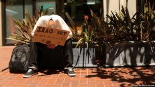 A man holds a sign as he seeks money in San Francisco, California
