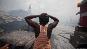 A Haitian merchant cries as she watches flames engulf her belongings at Port Market in Port-au-Prince, Haiti