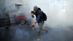 A demonstrator runs with gas mask as Turkish riot policemen use tear gas to disperse protesters, 31 May 2013