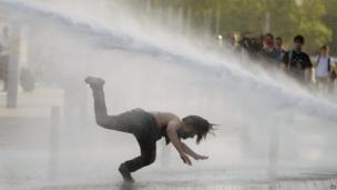 A man falls as riot police use tear gas and pressurized water to quash a peaceful demonstration at an Istanbul park, Turkey, 31 May 2013