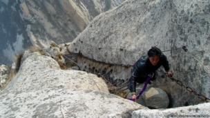Man climbs to Chang Kong Cliff Road in Shaanxi province, China