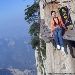 Woman poses on Chang Kong Cliff Road in Shaanxi province, China