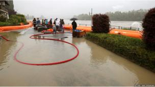 People stand behind a mobile flood protection wall as they look at the floodwater from the Rhine river in the northern Swiss village of Wallbach (June 1, 2013)