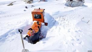 Sherman shovels snow away from a digger to get to a heater plug which will warm the engine overnight