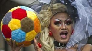A participant at the Gay Pride march in Sao Paulo holds up a fluffy football.