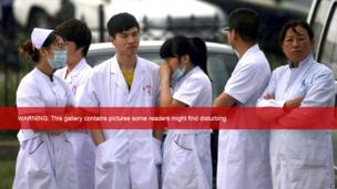 Medical staff wait near a poultry processing plant that was engulfed by a fire in Dehui, north-east China's Jilin province, 3 June 2013