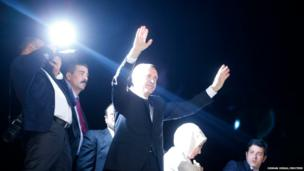 Turkey's Prime Minister Tayyip Erdogan waves to supporters after arriving at Istanbul's Ataturk airport