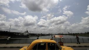 Rain clouds hover over as a cab plies through a bridge in Kolkata, India, Thursday, June 6, 2013. Monsoon rains are expected to arrive in the city in a week, according to weather officials