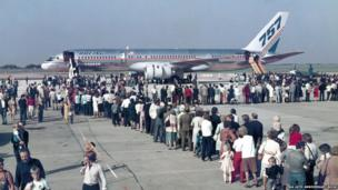Passengers queue to get on a Boeing 757