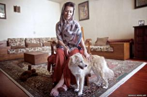 Iranian Shohreh poses for a picture with her Spitz dog Shiny in her house in Tehran