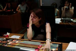 An employee wipes tears as she works with colleagues in the control room of ERT