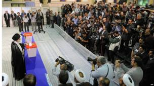A crowd of reporters and photographers record the Iranian Supreme Leader, Ayatollah Ali Khamenei, casting his vote in Tehran, June 14
