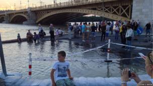 People stand along the side of the flooded river Danube in Budapest, Hungry. Photo: István G. Bartók