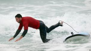 Alex Cuthbert riding a wave