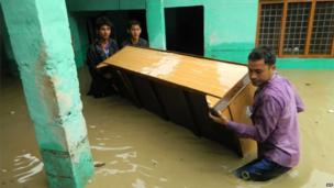 Indian people move furniture as homes floods due to the heavy rains in the northern state of Uttarakhand on June 17, 2013
