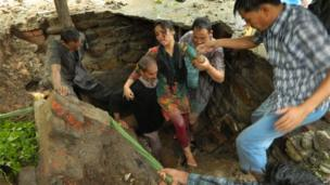Indian people engage in a rescue operation as homes collapse due to the heavy rains and floods in the northern state of Uttarakhand on June 17, 2013.