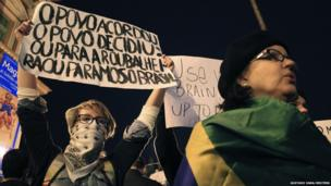 Demonstrators hold up signs during a protest outside the City Hall in Porto Alegre, 17 June 2013