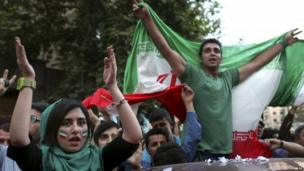 Iranians attend a street celebration, in Tehran, after their national soccer team qualified for the Brazil 2014 World Cup June 18.