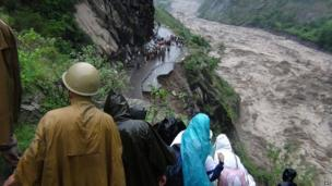 Indian people look at a collapsed road and the flooded river in the northern state of Uttarakhand