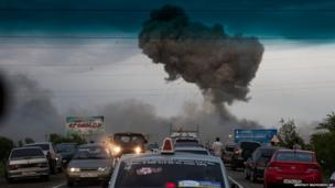 An explosion can be seen through the windscreen of a car at a military depot near Chapaevsk in Russia
