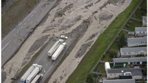 A police car and trucks blocked on a flooded Trans-Canada Highway in Canmore, Alberta, Canada, on 21 June.