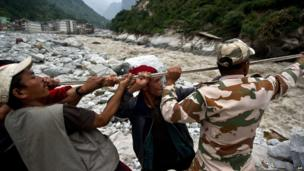 Indo-Tibetan Border Police (ITBP) personnel and local residents pull a rope to rescue stranded pilgrims on the other side of a river at Govind Ghat on 23 June 2013
