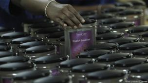 A worker arranges tea tins at a factory