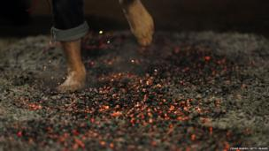 A reveller rushes through burning embers