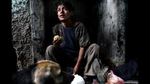 A boy who lives in a corner of an abandoned house with other kids and dogs in Lima, Peru. December 2012