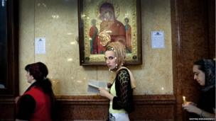 A young woman wearing a headscarve prays at Sameba Orthodox cathedral in Tbilisi, Georgia