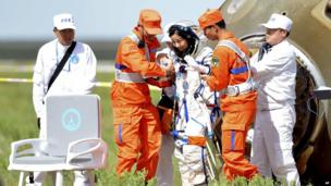 Chinese astronaut Wang Yaping exits the re-entry capsule after landing on 26 June 2013