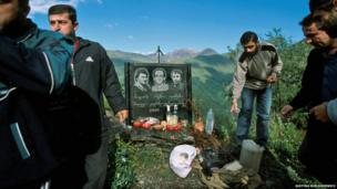 A group standing next to a stone memorial for three men who died in 2000