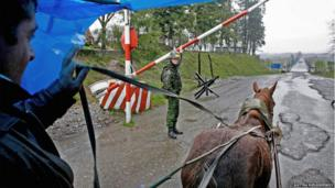 A soldier at a check point raises a barrier to let a man driving a horse and cart pass.